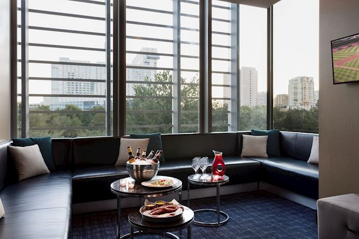 bench seating around a window with coffee tables for food and drink
